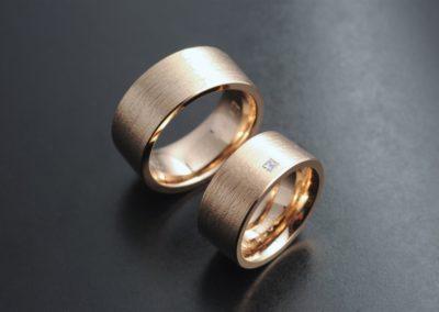 Eheringe: Rotgold, mit Diamant in Carré-Schliffform, längs gerillt